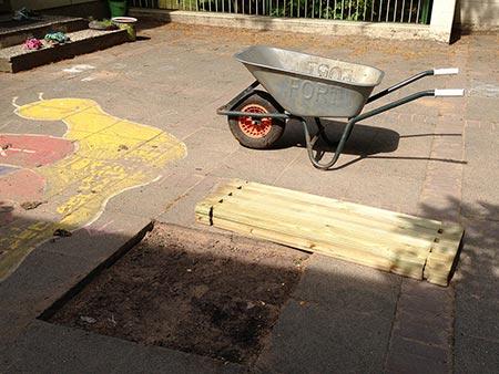 Hochbeet aufbauen, Schritt 1: Eine Schubkarre mit Steinen und der Bausatz stehen bereit.