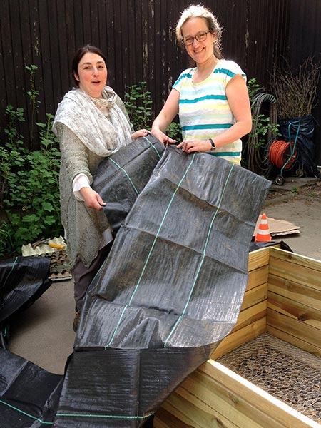 Zwei Mütter mit Netzfolie um das Hochbeet auszukleiden