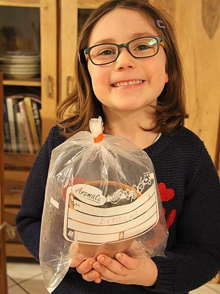 Kind hält ein Töpfchen in einem aufgeblasenen Gefrierbeutel in der Hand