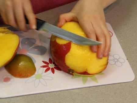 Nahaufnahme: Kind schält eine Mango.